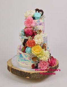 Bruidstaart met crème buitenlaag. Gedecoreerd met echte bloemen, macarons en chocolade.