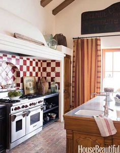 Cheery red and white tiles from Craftsman Court Ceramics are set off by dark soapstone countertops in this kitchen by Dana Lyon.   - HouseBeautiful.com