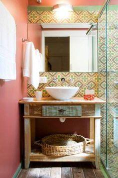 Repleto de cores, este lavabo tem ladrilhos hidráulicos, piso revestido de cruzetas de madeira de demolição e paredes na cor vermelha. O rebaixo de gesso com iluminação embutida e arandela acima da bancada garantem a luminosidade do espaço de 1,50 x 1,75 m. O projeto é da designer de interiores Rachel Avellar para uma casa em Campos do Jordão (SP).