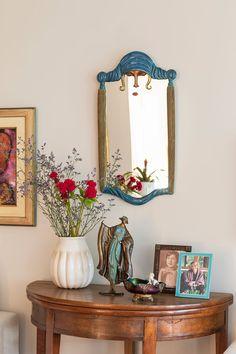 Decoração com personalidade, decoração colorida, detalhes da decoração da mesa lateral com flores, espelho e porta retrato.
