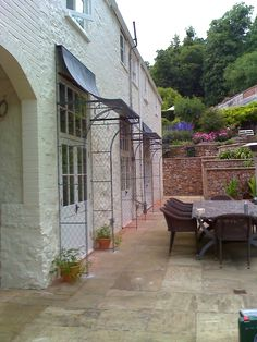 Triple porch design on a country cottage. Deep scoop door canopies with trellis side panels create a characterful charm to this property. Hand made porches from skilled craftsmen at Garden Requisites in Bath. http://www.garden-requisites.co.uk/