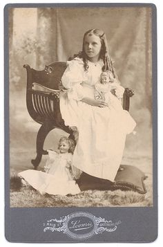 Gorgeous cabinet card of a darling girl posed with her two dolls.