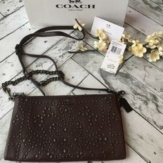 """Coach Crossbody Purse NWT Brand spankin new with tags!! Beautiful studded authentic Coach purse! Color is labeled as """"oxlips"""" but I would consider a deep burgundy. Leather strap with chain is detachable so you can carry as either a crossbody or a clutch. Includes gift box!                      ‼️‼️ NO Trades‼️‼️             offers appreciated thru the offer button.              〽️ercari always has listing at a lower price ! Coach Bags Crossbody Bags"""