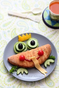 Prince Frog ~ Garlic oregano cheese bread from local bakery (or substitutes)* with tiny cheese circles green tomato , cucumber and olive eyes , cherry tomato ketchup mouth and cucumber feet . For the cheesy tongue- keep a cheese slice diagonally & cut out a long ribbon using a toothpick, make a cut on the bread and insert it gently