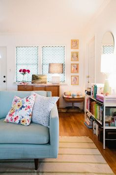 the couch hunt is on : blue // the blue couch and colorful books make the room feel friendly.