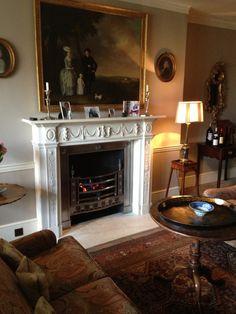 Beautifully carved mantel, art, rug, comfortable looking furniture, moody lighting (Georgian Regency Interiors)