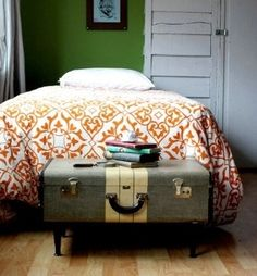 vintage suitcase with legs added to make end of bed blanket storage.