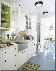So many fantastic things going on here!  Pop of color in the shelves.    Kitchen sink!  Colored floors!   Awesome appliances