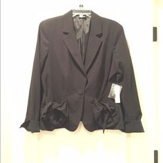 """Stylish Black One Button Blazer Black blazer with simple ties on each front pocket.  One button closure, rounded corner bottom hem.  Full length sleeve with 2 inch slit, also rounded corner hem - can be worn down or cuffed.  Solid back - no split.  Fully lined.  Outer shell / 62% polyester, 34% rayon, 4% spandex.  Lining / 100% polyester.  Machine wash cold / tumble dry low.  Jacket length from shoulder seam to hem line 24"""". Sleeve length from shoulder seam to hem line 25"""" Allen B. by Allen…"""