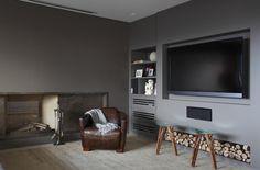 Neste projeto do escritório In House Designers de Interiores, o uso do cinza uniformizou o ambiente e criou uma boa base para o aparelho de TV. Na lateral, há um móvel embutido com nichos e um compartimento para adega, fechado com porta vasada