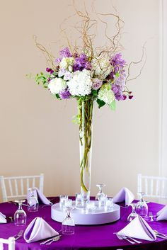 Tall Centerpieces in a Tall Pilsner vase with pink, white and blue floral and greenery with curly will shooting out of the top