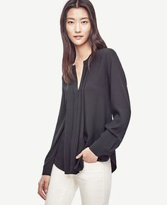 """Pretty pleats refine this modern essential, cast in a smooth knit and woven mix. Split neck. Long sleeves with button closure. Front knife pleats. Back flap pleats. Shirttail hem. Woven front, sleeves and back pleats. Knit back. 26 1/2"""" long."""