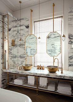 Octagonal brass mirror in front of window, Calcutta marble and brass vanity, brass vessel sinks.