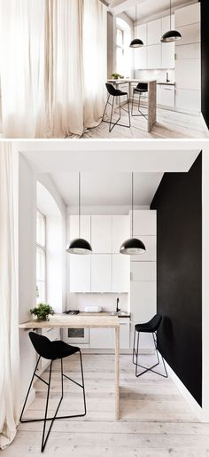 White and black kitchen in a tiny house with floor-to-ceiling windows, black light fixtures, and stools.