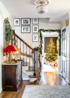 Christmas decor ideas | Modern meets traditional Christmas foyer with red amaryllis and real looking faux garland. #christmasdecor #entryway
