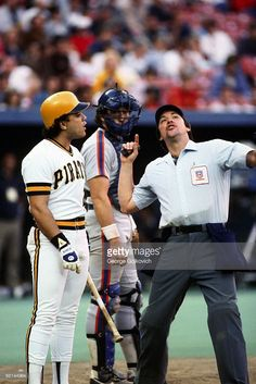 Major League Baseball umpire Dana DeMuth (R) ejects Sixto Lezcano of the Pittsburgh Pirates as catcher Gary Carter of the New York Mets looks on during a game at Three Rivers Stadium in 1985 in Pittsburgh, Pennsylvania.