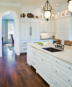 Stunning white kitchen accented with the dark, wood floors.
