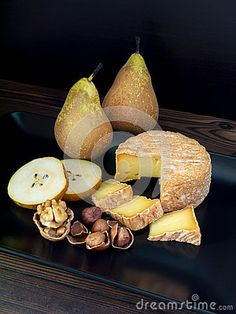 Soft washed-rind cheese, walnut, hazelnuts and pears on the black plate