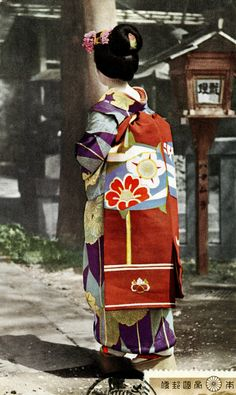 https://flic.kr/p/dSTRzq   Itomaki Obi 1939   This is a vintage postcard by T. Hasegawa, postmarked Showa 14 (1939). It shows a Maiko (Apprentice Geisha) wearing a persimmon coloured Darari Obi (Dangling Sash) with a stylised Itomaki (Thread Spool) motif. Itomaki were wooden spools used for winding and unwinding the silk thread in looms for making traditional Japanese garments. Multi-coloured Itomaki were also considered to be a charm against evil spirits.