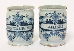 A pair of English delft miniature Dry Drug Jars, c.1700, each cylindrical body painted with a label inscribed either 'E centaur; M;' or 'B Arcæi' on a complex cartouche above a seraphim, posies, and below peacocks, 10.1cm (2)  The first: electuarium centuarium minus (honey-based medicine containing ground flowering tops of herbs); the second, balsamum arcaei, was named after its discoverer, the Spanish physician, Francesco Arcaeus (1493-1567).