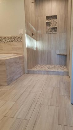 """Contemporary shower design. 12x24 wall tile set vertical """"stacked"""". Complete with a floating corner bench and pebble pan. Pan tile was set individually and not from a mat. Work done by Glueks Custom."""
