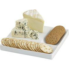 Peynir ve kraker servis tabağı, beyaz porselen yüzeyinde peynir, salam, aperatif ve krakerleri bir arada servis ediyor.