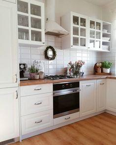 Białe witrynki w aranżacji kuchni z drewnianą podłogą - Lovingit.pl