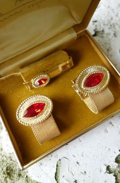 A handsome pair of mens vintage cufflinks by Tally Hi. They are gold metal in an oval shape with red rhinestones in the center. New old stock. $35