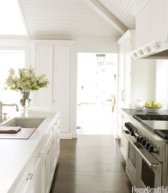 The wide-plank heart pine floor, stained a dark chocolate brown, conveys a feeling of age and keeps an all-white kitchen from floating away. Viking's 60-inch dual-fuel range in stainless steel is the only visible appliance.   - HouseBeautiful.com