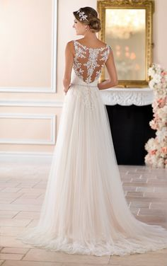 From Stella York, this grecian column wedding dress with high lace neck and illusion back is the casually cool wedding dress brides are looking for! Delicate lace covers the bodice and floats down onto the soft multi-layer French tulle skirt to elongate and create interest. The tulle train features a whimsical lace detail trim, adding to the drama of this wedding dress. An illusion back mirrors the lace on the bodice with a cameo pattern that flatters all figures and adds depth to the…