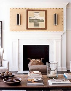 A family room cries out for a TV, but Stilin didn't want one above the mantel. Instead he made a simple but dramatic piece of art: He covered a board with Madagascar cloth and nailheads, then attached 1950s French sconces and a Mark Wilson landscape.   - HouseBeautiful.com
