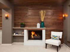 As seen on HGTV's Elbow Room, this basement was renovated by licensed contractor Chip Wade to include a new guest suite for visitors, home beer-brewing area and entertaining space for the whole family. This is the suite's modern lounging area with a deep fireplace. The space has clean, modern feel that is warmed up by the wood accent walls.