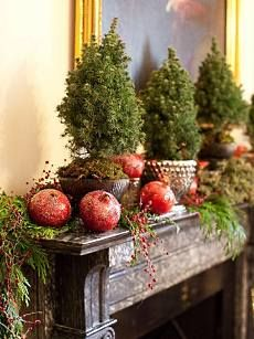 pomegranates provide a striking con-  trast to the evergreen boughs and   mini pine trees on the mantel at left. Tucked into the evergreens are sprigs of tiny red crystals that echo the col-  or of the pomegranates.
