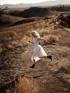 The model runs through an open field in a white dress for Elle UK