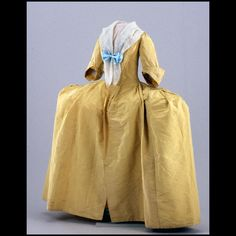 """Woman's gown, yellow silk with wide hoop skirt 1740-1750 Origin: England Overall length 58"""". Waist approx 19 1/2"""" without stomacher. Width approximately 36"""". Textile 19 7/8"""" wide from selvage to selvage. Heavy ribbed silk; tabby linen bodice and sleeve lining; thin tabby silk skirt lining; silk ribbon hem binding. Museum Purchase DS2000-0324"""
