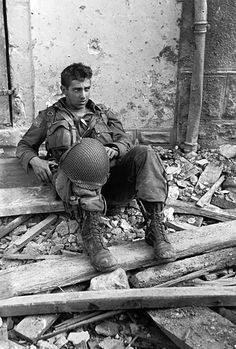 A U.S. Army soldier pauses for a rest amongst the ruins during the Battle of Normandy. Saint-Sauveur-le-Vicomte, Manche, Lower Normandy, France. 16 June 1944.