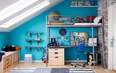 Pokoj pro teenager se stříbrnou vysokou postelí, pod níž je psací stůl a komoda.