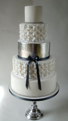 White wedding cake with silver leaf middle tier, and swarovski crystal centered blossoms. The trim is also Swarovski crystal.