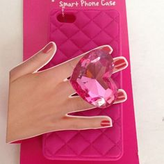 """ADORABLE """"ring"""" PHONE CASE FOR iPhone 5-NWT Brand new iPhone 5 smart phone case featuring a big blingy pink heart ring on back to use as a """"handle"""". Looks so cute but also practical by helping to prevent from dropping your phone.  Front of case is open.  Made of silicone so it easily slips on and off your phone. Ring """"band"""" is stretch so it fits all sizes. Never used, still in packaging. Accessories Phone Cases"""