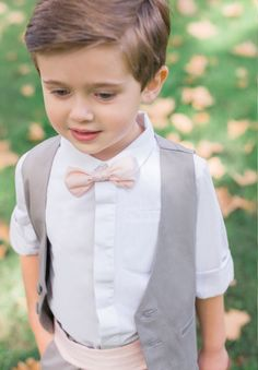 Ce charmant garçon d'honneur porte notre ensemble gris souris accompagné d'un noeud papillon Roméo rose poudré et d'une ceinture Théo assortie