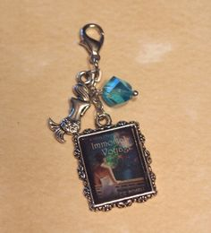 A Book Cover keepsake! Custom charm made with 1 frame with your graphic Book cover sealed in resin, 1 regular charm and a cut crystal bead.