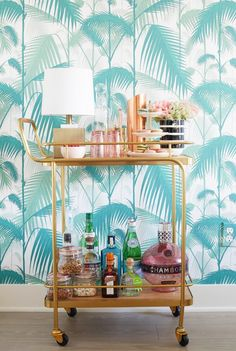 A space with tropical wallpaper, and a gold well-styled bar cart