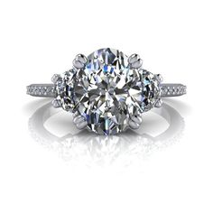 Moissanite three stone engagement ring featuring an oval, 2.10 ct True Light Moissanite, G/H color and flanked by two half moon True Light Moissanite, each .25 ct. Diamonds, 20, G/H SI1, .07 ct Don't
