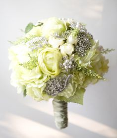 this wedding bouquet has added interest and depth with the addition of silver, pearl and crystal brooches. Very pretty and elegant.