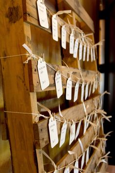Our place cards for tables. Recycled wooden pallet, string, mini clothes pins & ivory name cards.