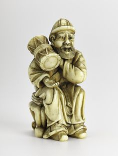 Netsuke of carved ivory, a Korean man sitting on a three-legged stool beating a tsuzumi drum held on his right shoulder, unsigned: Japan