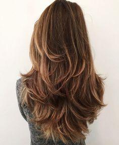 Ragazza con un taglio di capelli castani scalati, volume alle radici