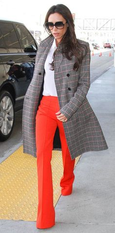 Victoria Beckham delivered another one of her posh jet-setting outfits, landing at JFK in a smart white button-down and wide-leg orange pants under a sleek checked topper.