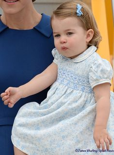 Now to what the Prince and Princess wore for their big day. Charlotte wore a pastel blue floral dress. It is a traditional little girl's style with puffed sleeves, pin tucks and smocking on the bodice, and a Peter Pan collar. What Kate's Kids Wore Smocked Baby Clothes, Girls Smocked Dresses, Baby Girl Dresses, Prince William Family, Prince William And Kate, Princess Kate, Little Princess, Punto Smok, English Royal Family