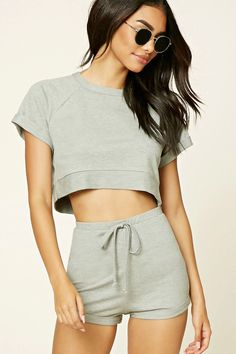 A French terry knit crop top featuring a round neckline, short cuffed raglan sleeves, side slits, and a boxy silhouette. Matching shorts available.